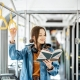 Young woman reading book while standing in the modern tram, happy passenger moving by comfortable public transport, Image: 433660659, License: Royalty-free, Restrictions: , Model Release: yes, Credit line: Profimedia, Alamy